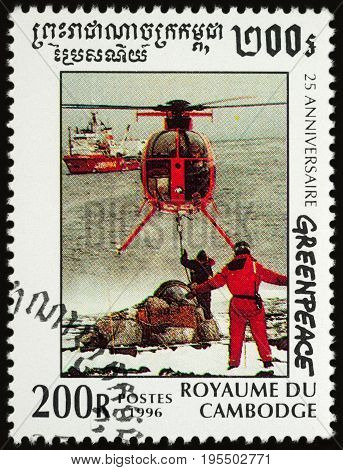 Moscow Russia - July 15 2017: A stamp printed in Cambodia shows the helicopter transports cargo from ship to shore in Arctic series