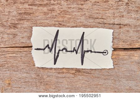 Paper with image of heart impulses. Heartbeat impulses on paper sheet, wooden table.