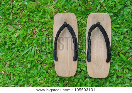 Top view close up old wooden sandal with a thick sole on green grass.