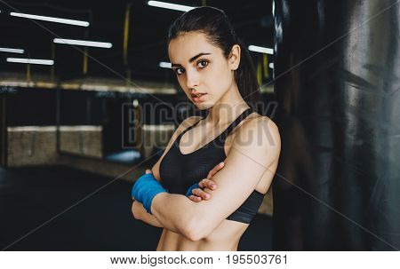 Young sporty girl with crossed arms seriously looking at camera. Focused woman standing with wrapped fists with blue bandage tape and looking at the camera