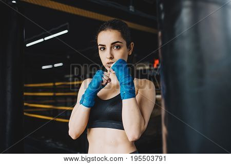 Pretty young woman with wrapped arms standing in a boxing stance. Confident caucasian girl is ready for a fighting training. Close up