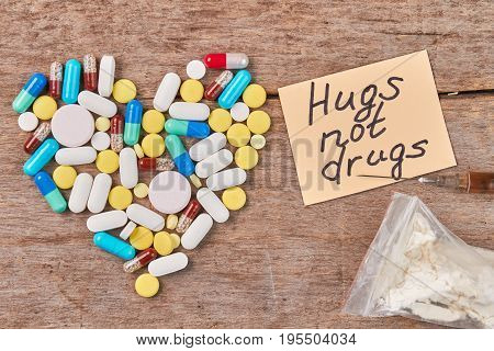 Message hugs not drugs. Heart from colorful pills, note, narcotics, wooden table.