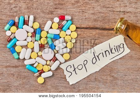 Stop drinking and start new life. Pills shaped heart, message, bottle neck, wooden table.
