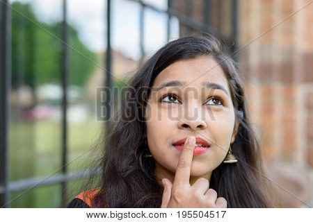 Young Indian woman puzzling a problem looking up into the air with her finger to her lips and a contemplative expression outdoors in front of railings