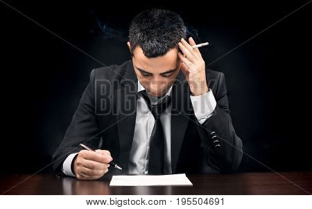 Young Businessman In Depression Smoking And Reading Contract Before Signing