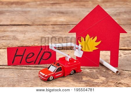 Flaming house, cigarette, toy fire truck. Message help, toy lorry, flame, wooden background.