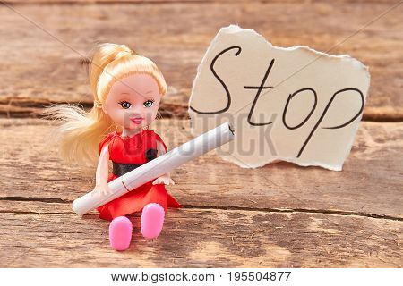 Toy doll holds a cigarette. Doll with cigarette, message stop, old wooden background. Metaphor concept stop smoking.