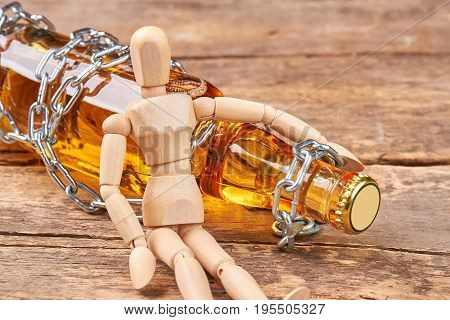 Human wooden dummy sitting with bottle. Bottle wrapped in chain, wooden human mannequin, old wooden background. Concept of alcohol addiction.
