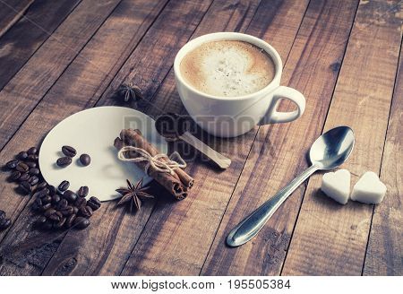 Still life with coffee. Photo of coffee cup cinnamon sticks coffee beans anise sugar spoon and coasters on vintage wood background.