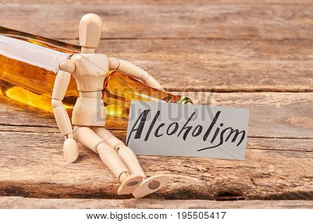 Human wooden dummy and alcohol. Alcoholism ruins the organism.