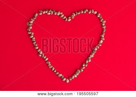 Background with macro detail of cannabis (hemp) seeds forming a heart over red background - medical marijuana concept