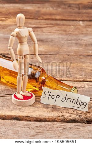 Stop drinking and become thinking. Human wooden dummy, alcohol beverage in glass bottle, message, wooden background.