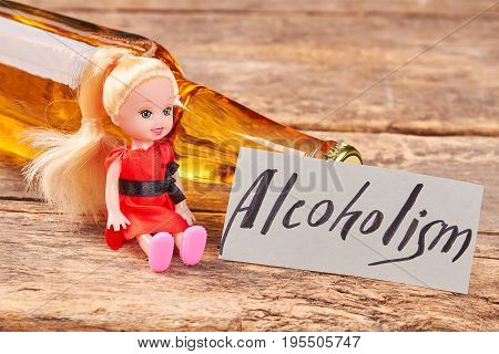 Lying bottle, doll, paper message. Full bottle of beer, toy, text alcoholism, wooden background.