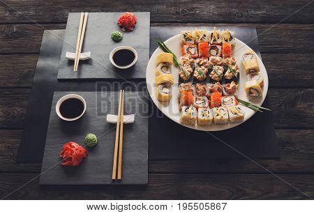 Japanese food restaurant, california rolls and sushi platter. Set with chopsticks and soy sauce, on black background