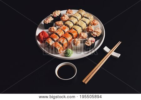 Sushi and rolls set on black background, pov view. Gunkan and salmon in japanese restaurant