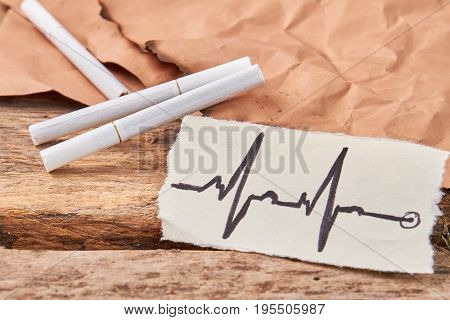 Image of cardiac impulses and cigarettes. Cigarettes, old burnt piece of paper, image of heartbeat. Smoking tobacco cigarettes leads to heart diseases.