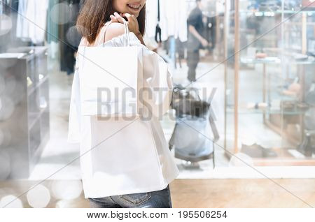 Woman holding bags are shopping in the mall. Shopping concept is happy and Can try the product yourself.