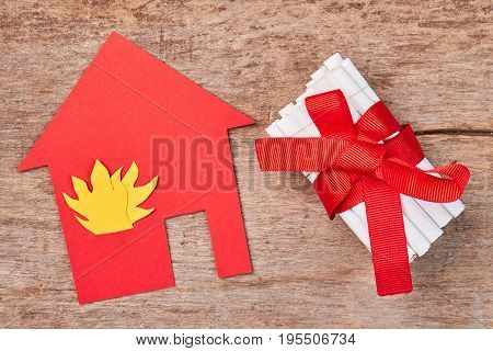 Red cardboard building, pile of cigarettes. Paper house with flame, tobacco cigarettes with red bow, old wooden background. Concept of fire from cigarettes.