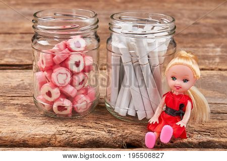 Candies, cigarettes, doll, glass jars. Metaphor concept of cigarette addiction. Do not smoke, buy your child sweets.