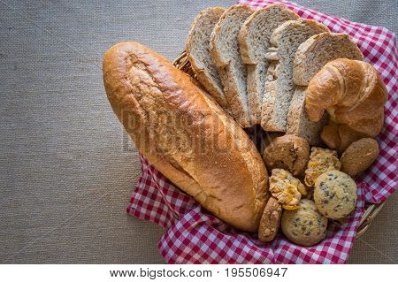 Fresh bread sliced bread french bread cookie and croissant in the basket.