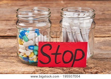 Pills, tobacco cigarettes, message stop. Stop unhealthy lifestyle concept.