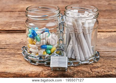 Cigarettes, pills, chain, wooden background. Jars with pills and cigarettes wrapped in metal chain on wooden background. Concept of tobacco cigarette addiction.