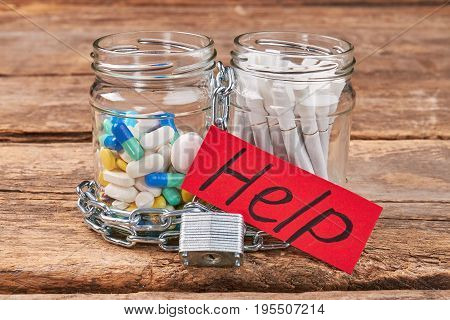 Cigarettes and pills in jars. Help to stop cigarette smoking. Nicotine is poisoning and effects body.