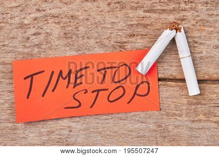 Broken cigarette, message, wooden background. Time to stop smoking cigarette concept.
