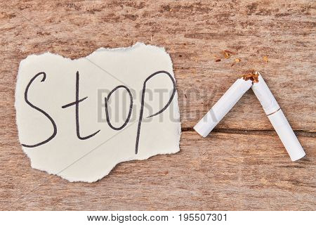 Broken tobacco cigarette, message stop. White cigarette with filter broken. How to stop nicotine addiction.