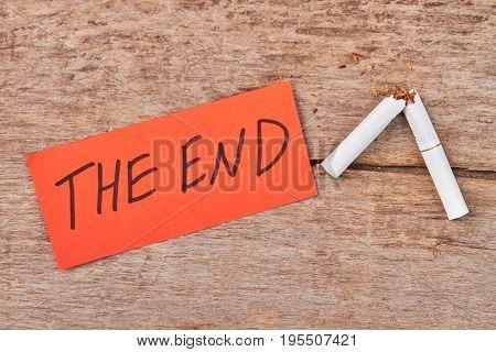 Message the end, broken cigarette. White broken tobacco cigarette on wooden background, top view.