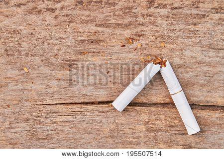 Broken tobacco cigarette. Broken white tobacco cigarette lying on old wooden background. Stop smoking cigarette concept.