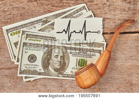 Cost of tobacco cigarette addiction. Dollars, tobacco pipe, image of heartbeat, wooden background.