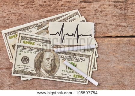 American money, cigarettes, heartbeat image. The cost of cigarette smoking.