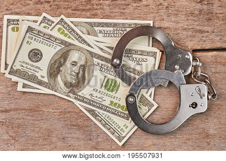 Stack of money and handcuffs on table. Law punishment of criminal.