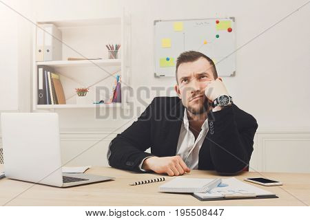 Young stressed and overworked business owner. Businessman in modern office upset with employees ask for attention with devices. Unhappy worcaholic job problems concept.