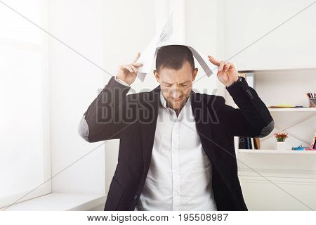 Too much paperwork. Exhausted businessman holding documents over head, standing at office workplace