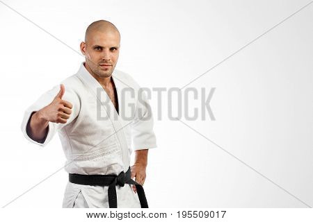 Young man fighter in a white kimono with black belt for judo jujitsu posing on isolated white background holding a thumb up