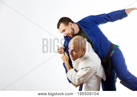 Two young men in a blue and white kimono fight judo Jiu Jitsu on an isolated white background