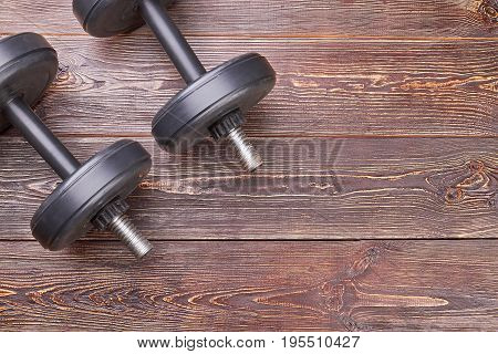 Weight lifting objects on wooden floor. Metal equipment for heavy fitness training.