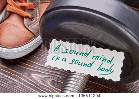 Sound mind in a sound body. Dummbells, sneakers, message close up.
