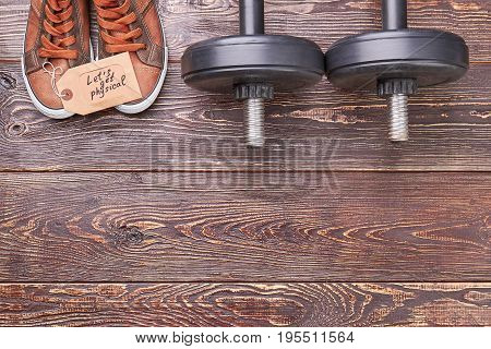 Be in physical form with dumbbells. Dumbbells, male shoes, paper message, copy space.