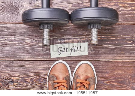 Get fit with physical exercises. Dumbbells, message, sport shoes, wooden background.