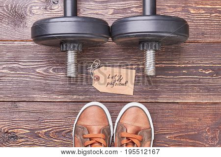 Trainer dumbbells and shoes in gym. Get physical with hard training.