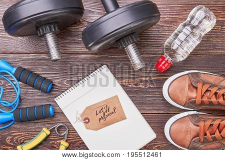 Sport accessories and paper notebook. Notebook, message, expander, jumping rope, dumbbells, water, sneakers, wooden background.