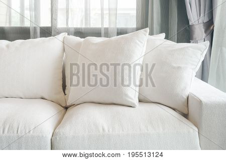 White Color Sofa And Pillows With Sheer Curtain In Background