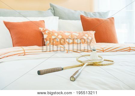 Modern Bedroom Interior With Orange And Gray Pillows With Rackets And Shuttlecock On Bed