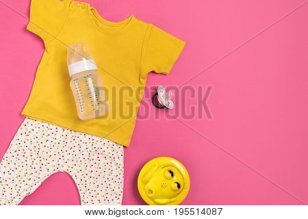Yellow children's costume, bottle and orthodontic pacifier on a pink background. Top view. Copy space. Flat lay. Still life