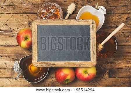 Rosh hashanah jewish new year holiday celebration concept. Honey and apples over wooden background. Top view