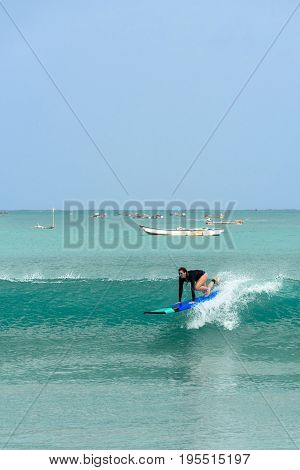 10/06/2017 Pantau Mawun Lombok Indonesia. Young woman learns to surf on a long board on learner waves in a paradise location.