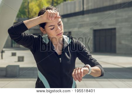 Young female active exercise workout on street outside checking time